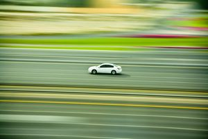 a blurred photo of a car on a racetrack