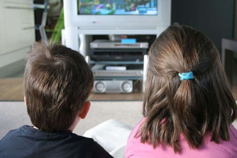 A young boy and girl watching television