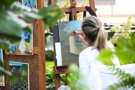 Woman painting on a canvas outside.