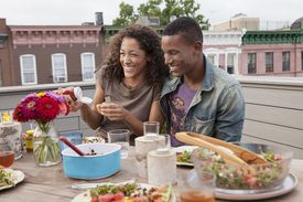 Couple eating at a picnic table at a roof party
