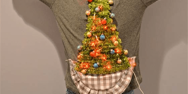 A man wearing an ugly Christmas sweater with a tree on it