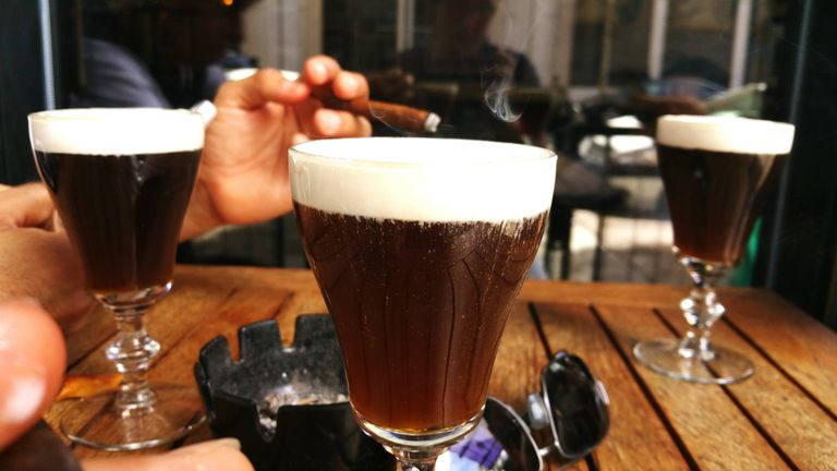 Man Smoking With Irish Coffee On Table At Cafe