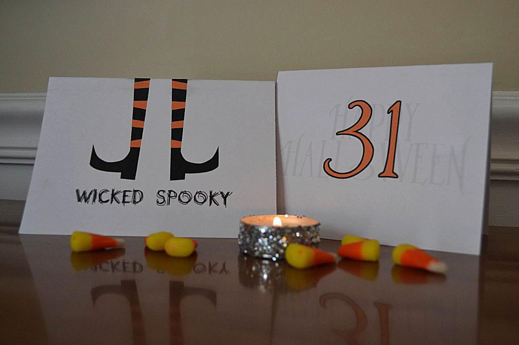 Two Halloween cards sitting on a table with candy corn and a candle.