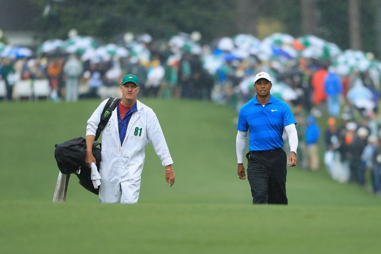 Tiger Woods walks with caddie Joe LaCava on the first fairway during the third round of the 2018 Masters Tournament.