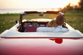 Rear view of young couple sitting in convertible car at sunset.