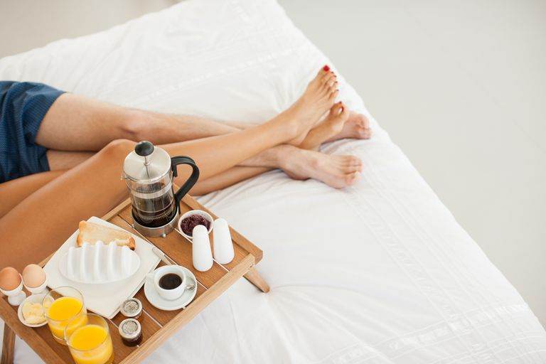 Couple in bed together with breakfast and juice