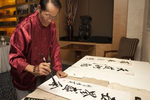 Elderly man painting traditional Chinese calligraphy.