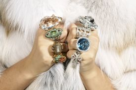 Young woman wearing fur coat and diamond rings, close-up, mid section