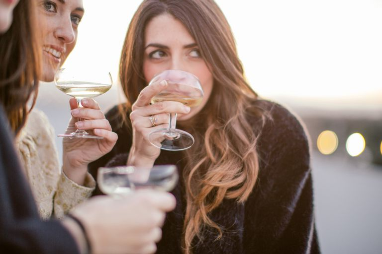 introverted woman drinking wine with friends