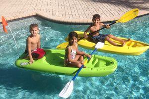 Kids in kayaks in a pool