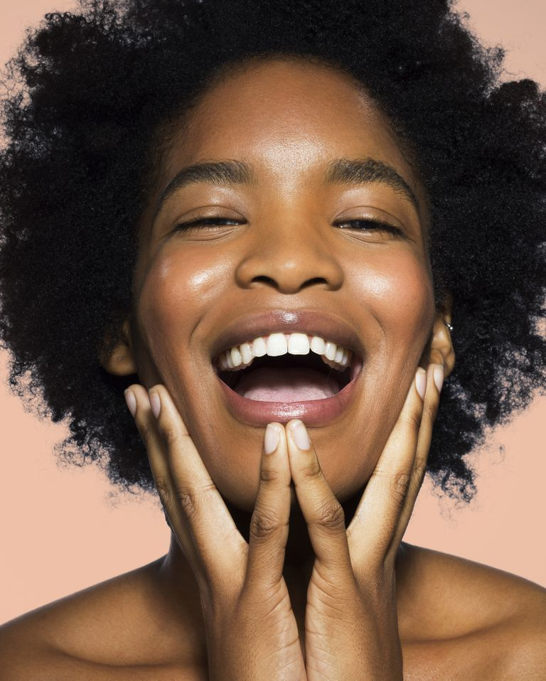 Young black woman with curly hair laughing into the camera