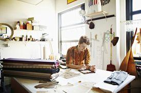 Designer in studio studying data on digital tablet