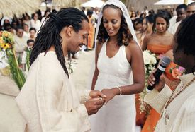 The groom places a ring on the bride's finger during a wedding ceremony