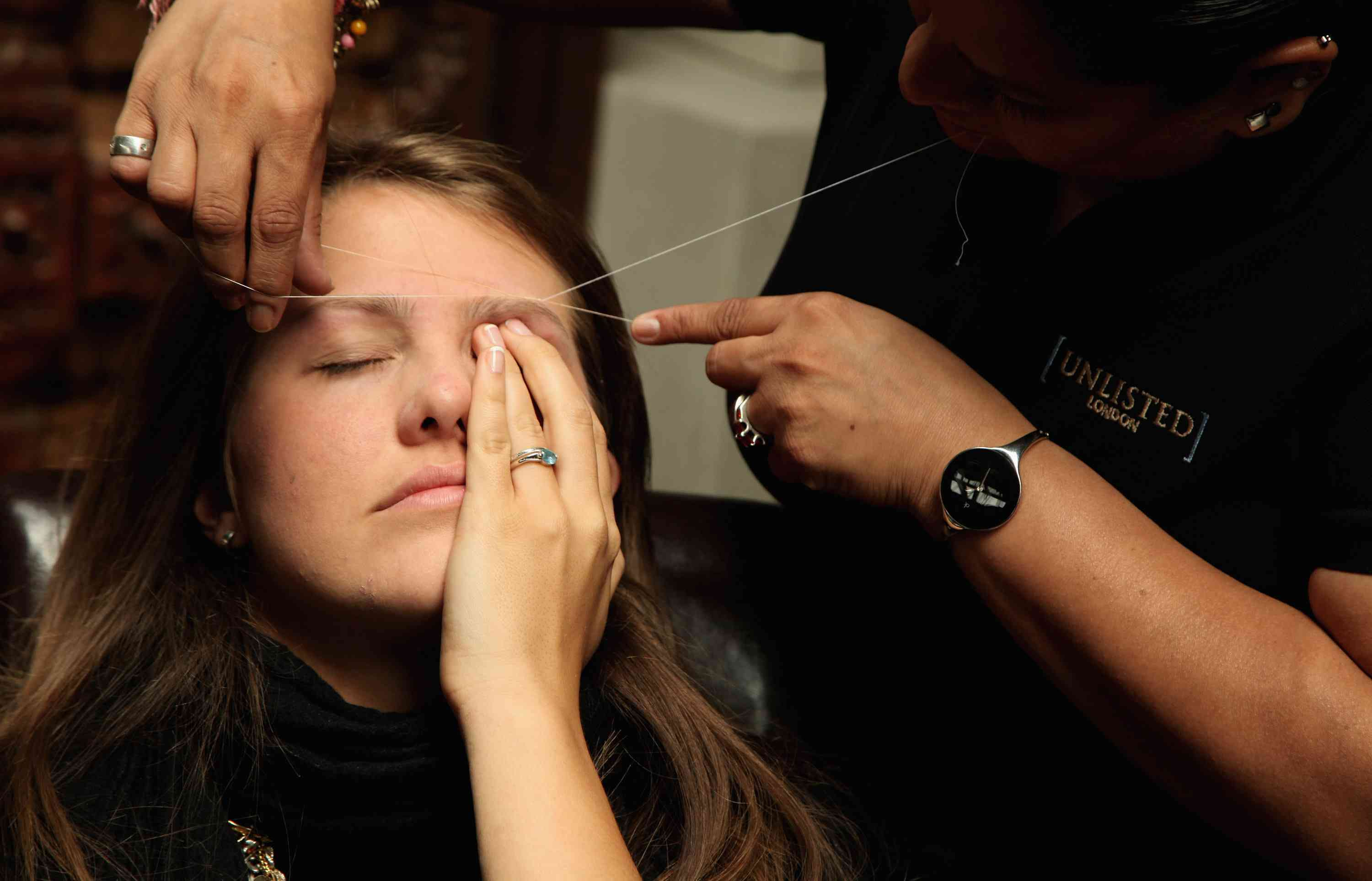A woman has her eyebrows threaded at the Designer Couture Trunk Show hosted by Noelle Reno at The Collection in London, England.