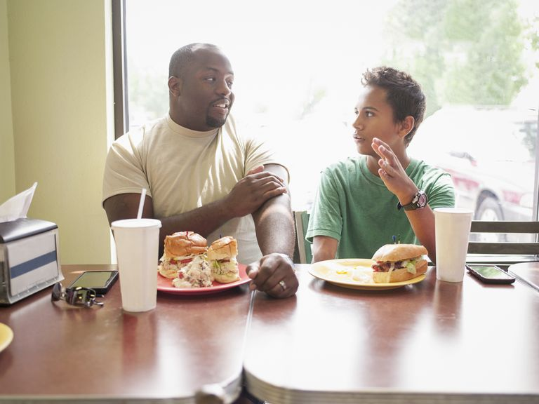 Father talking to teenaged son in restaurant