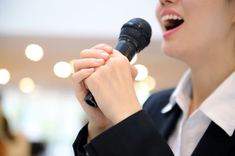 Close up of businesswoman with microphone speaking