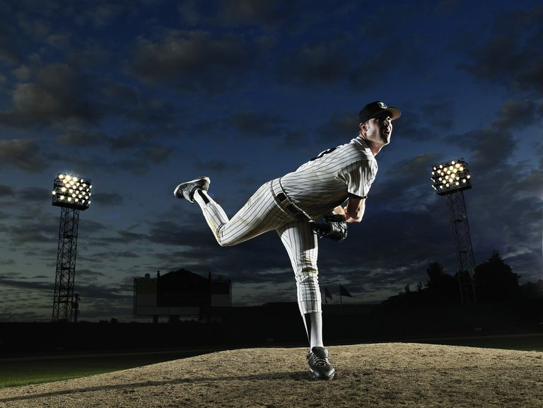 A baseball pitcher illuminated against a night sky