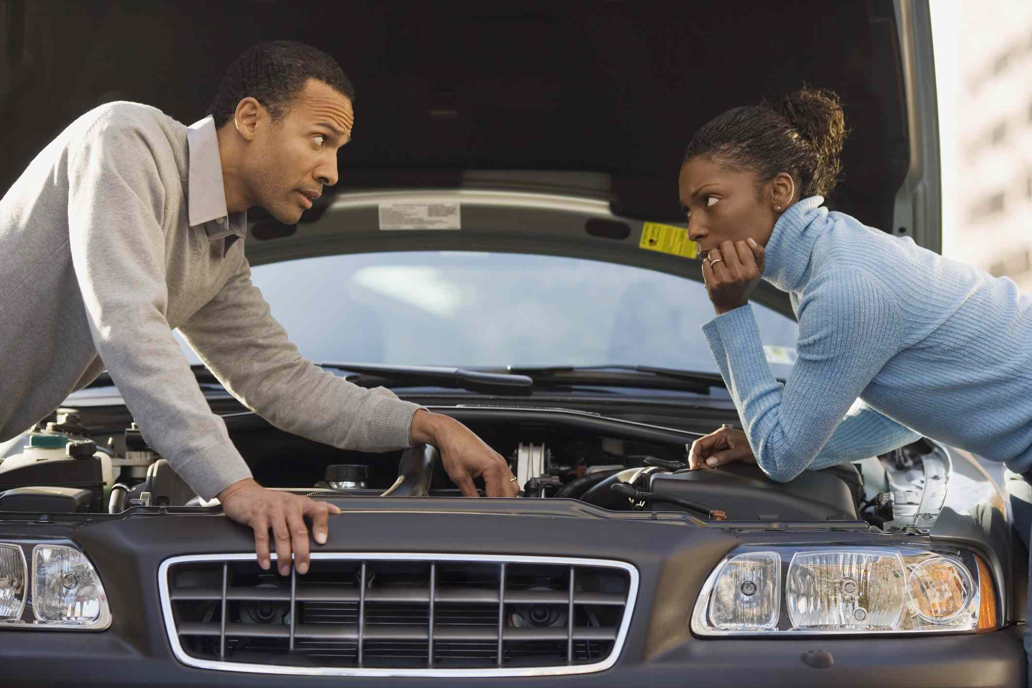 Man talking to woman over car