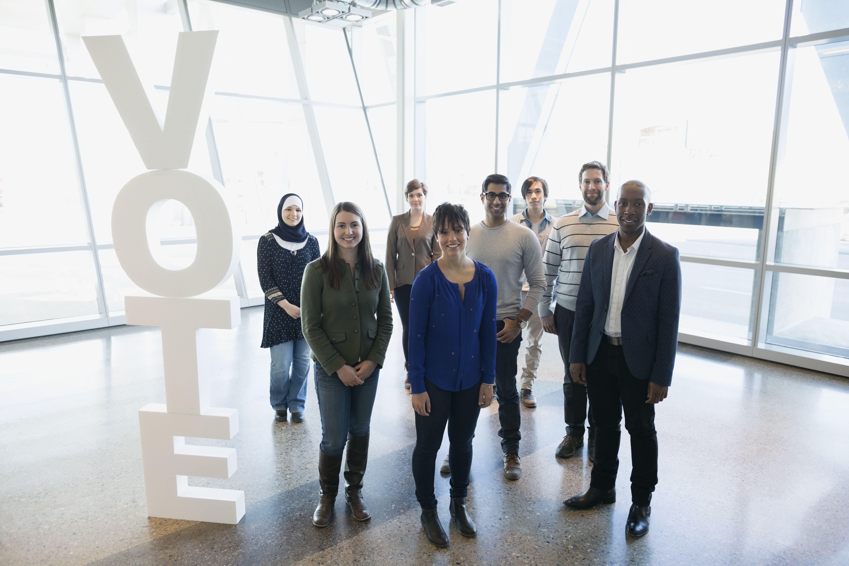 Portrait diverse group near Vote text