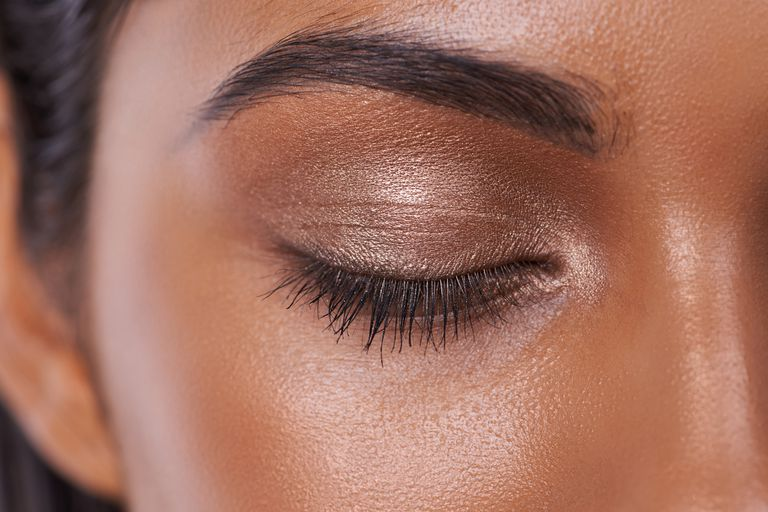 Close up of a woman of color with a shimmery eye and perfect brows