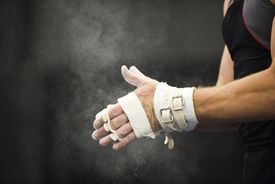 Gymnast applying chalk power to hands in preparation.