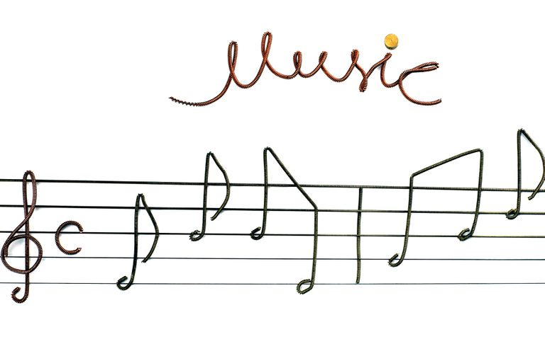 Musical notes, treble clef, and common time signature made from pieces of guitar strings