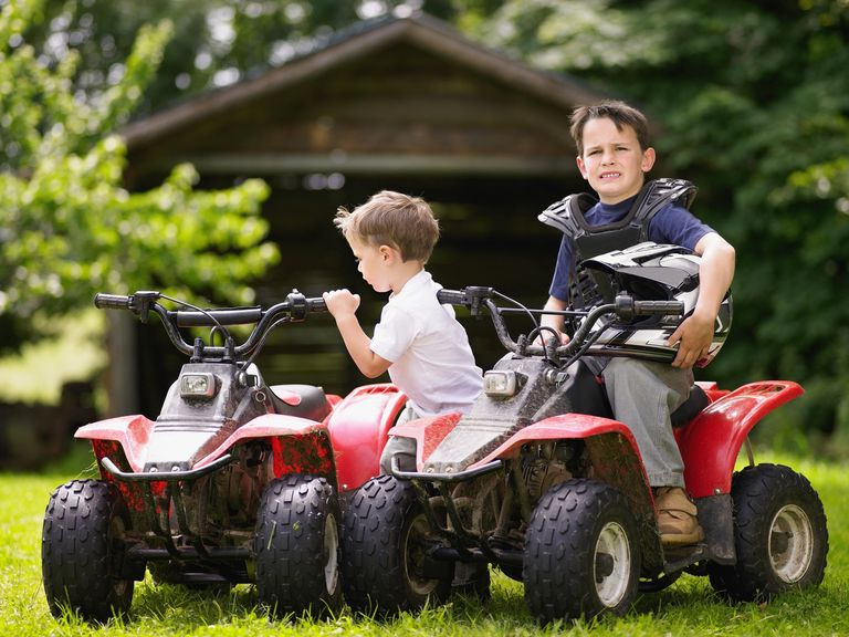 Two boys on quad bikes