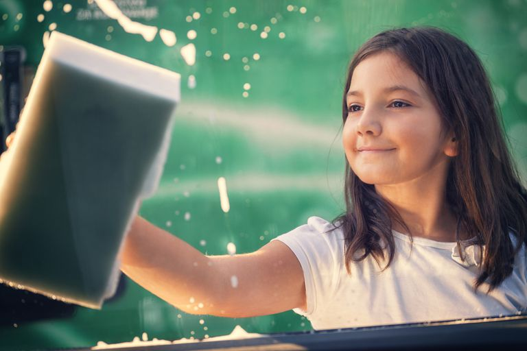 Little girl washing car window, view from inside
