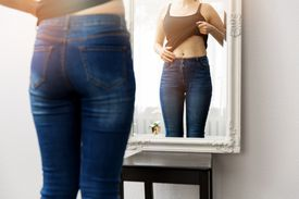 Woman in jeans looking in mirror at stomach