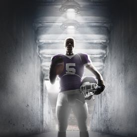 African American football player standing in hallway
