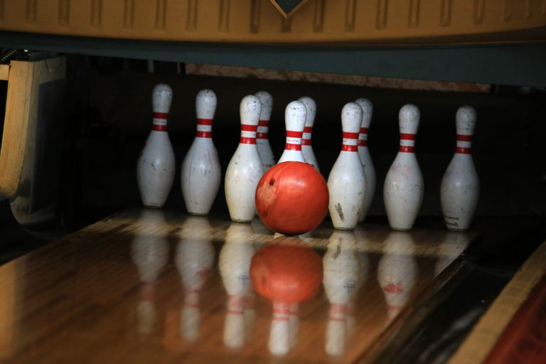 Bowling ball about to knock down pins