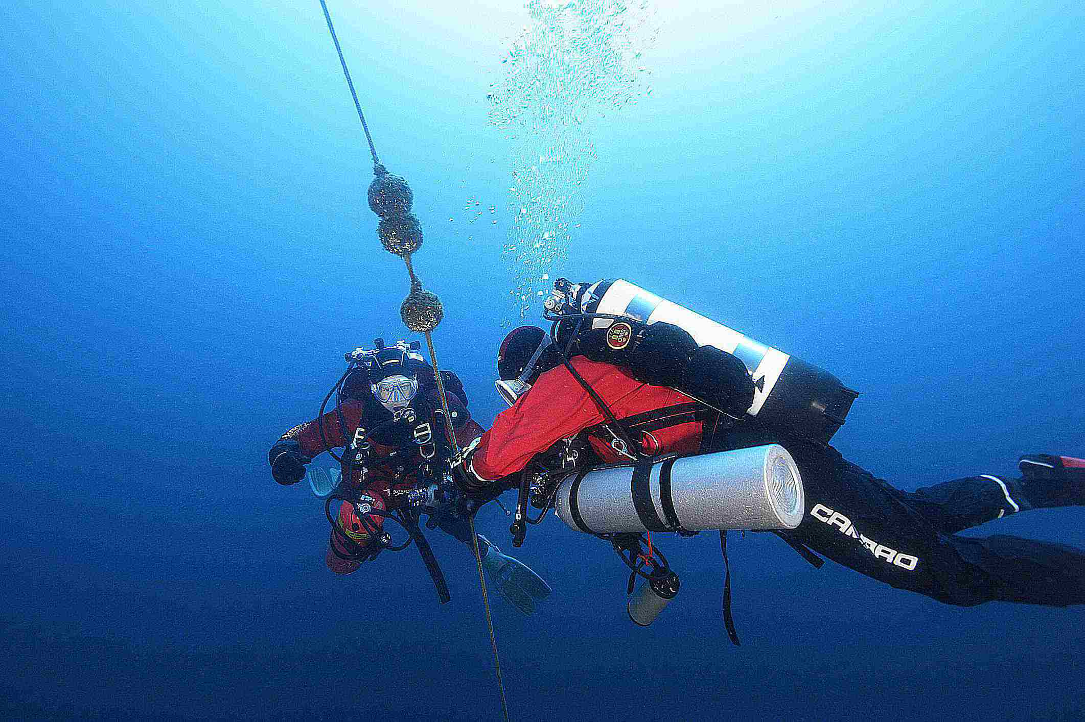 Technical divers using drysuits underwater