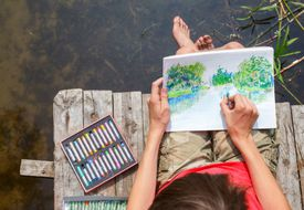 Kid drawing a summer landscape with a forest lake
