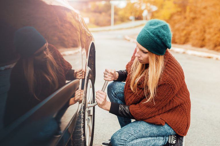 Woman using a lug wrench to remove a car tire on the side of a road