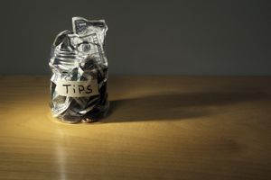 Tip jar stuffed with paper currency