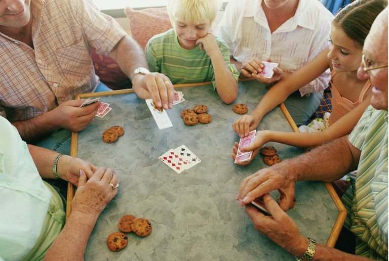 Family gathered around table playing cards.