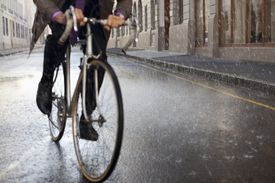 A man riding a bike in the rain.