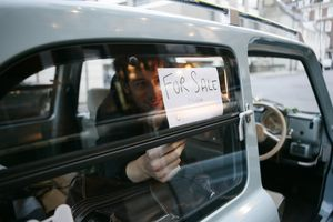 Man putting up 'for sale' sign in car