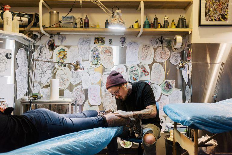 A tattoo artist working on a customer's leg.
