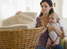 A picture of a woman folding laundry while holding a baby