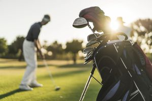 Close-up of golf bag with golfer in background