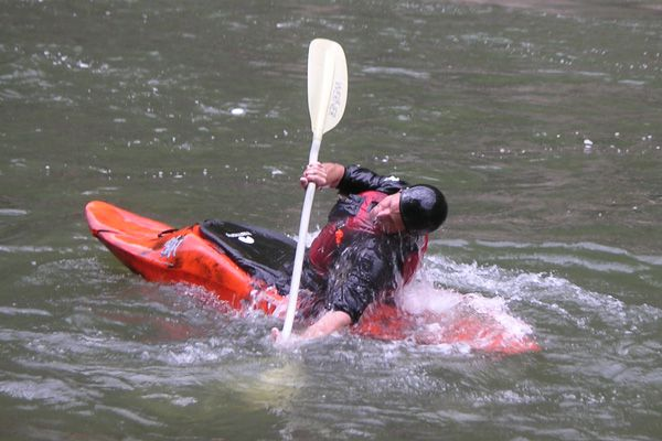 A kayaker emerges from the water after successfully rolling over