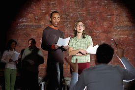 Man and woman on reading script onstage.