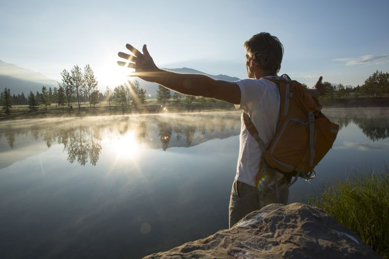 Man spreads arms wide across mountain lake