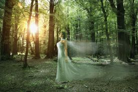 Blurred motion of elegant Hispanic woman in forest