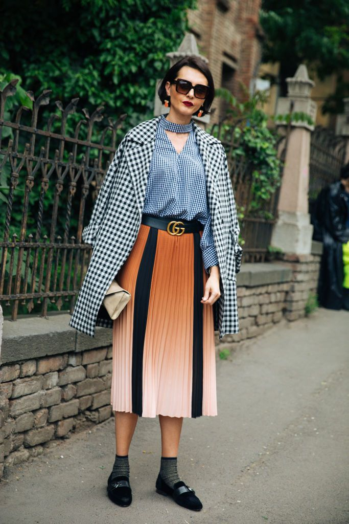 3d55a64c8b6 Woman wearing a gingham coat and top with a pleated skirt in orange and  black