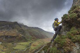 Mountaineer climbs steep mountainside