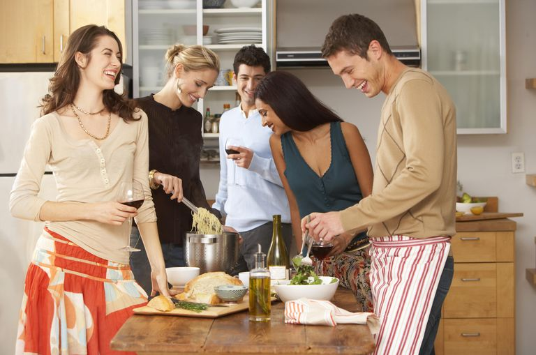 Group of young people in kitchen, couple preparing food, laughing