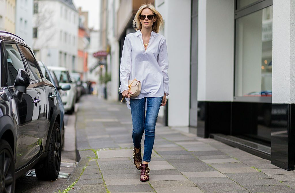 Supermodel in jeans and white shirt walking on a sidewalk