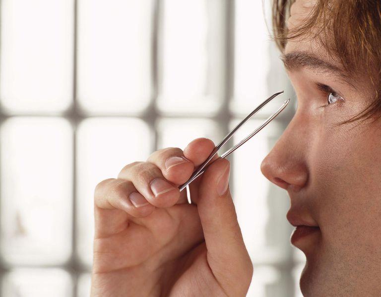 Man plucking eyebrows